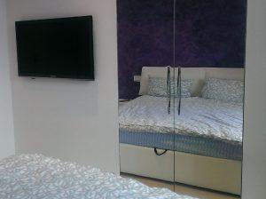 TV og spejlskab i soveværelse
